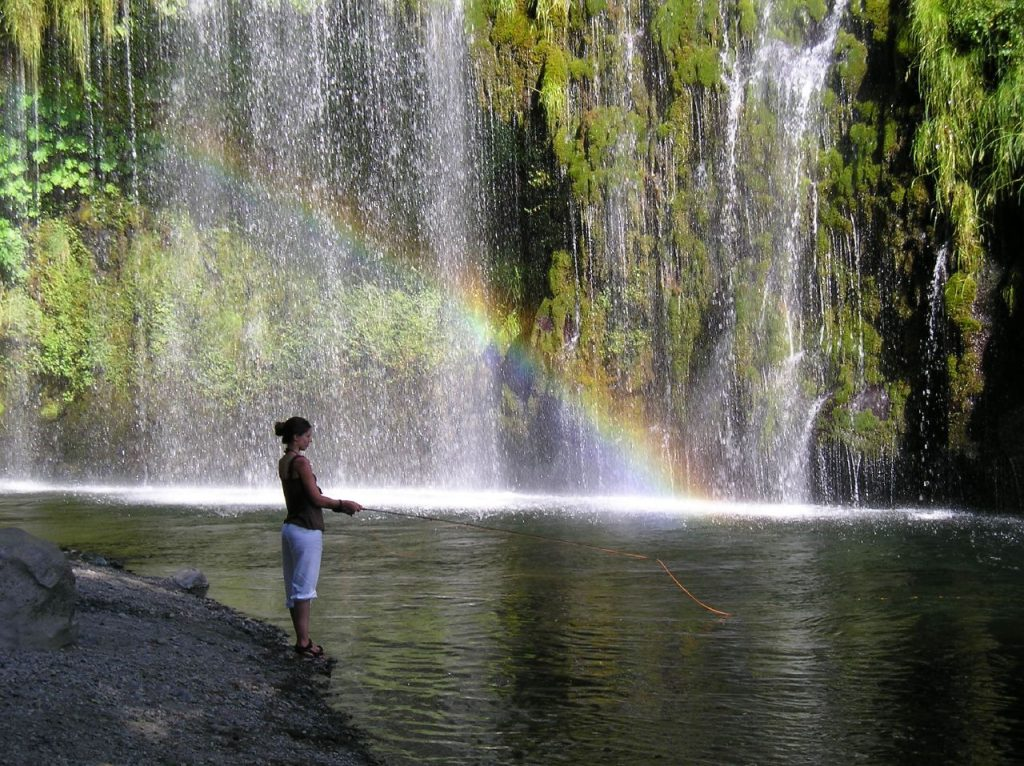 A woman fly fishes on the Upper Sacramento River with a rainbow formed in the waterfall behind her.